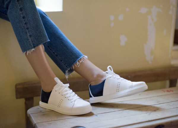 Someone in jeans wearing white and navy sneakers