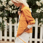 Blonde woman wearing an ochre jacket and white shorts