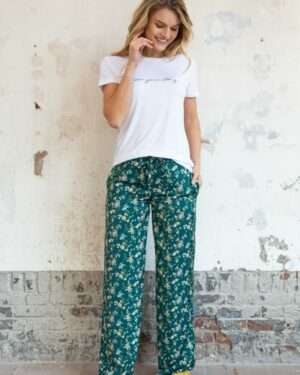 Woman wearing a white t-shirt and green flower palazzo trousers