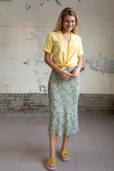 Woman wearing a yellow blouse with short sleeves with a flowered skirt