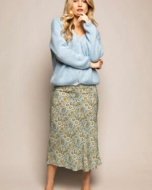 Woman wearing a light blue knitted cardigan and a flowered skirt