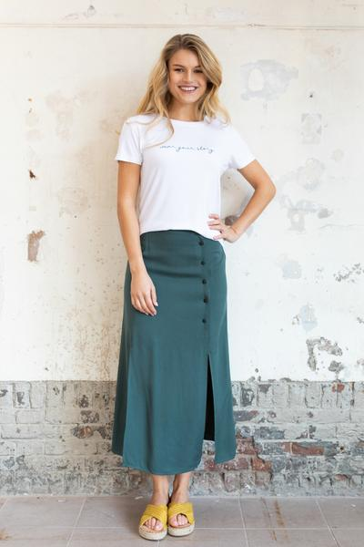 Woman wearing a green skirt with splits and a white t-shirt