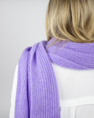 Woman wearing a purple scarf and a white blouse, back view