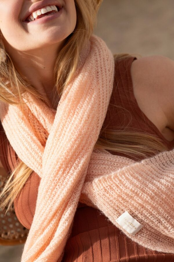 Woman smiling wearing a soft peach scarf