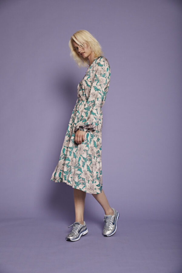 Girl wearing a midi length dress in a flower print in light pink and green
