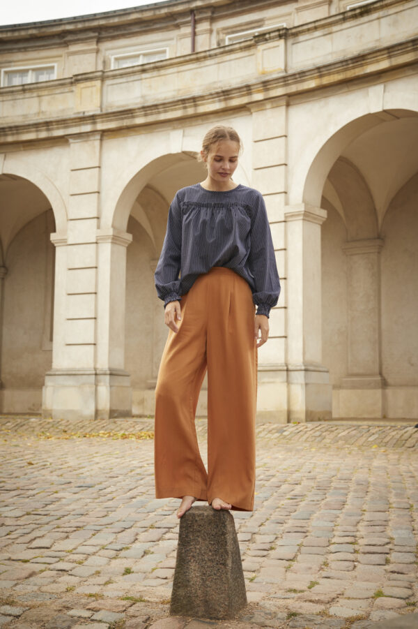 Girl standing on a pole wearing a navy blouse with wide trousers