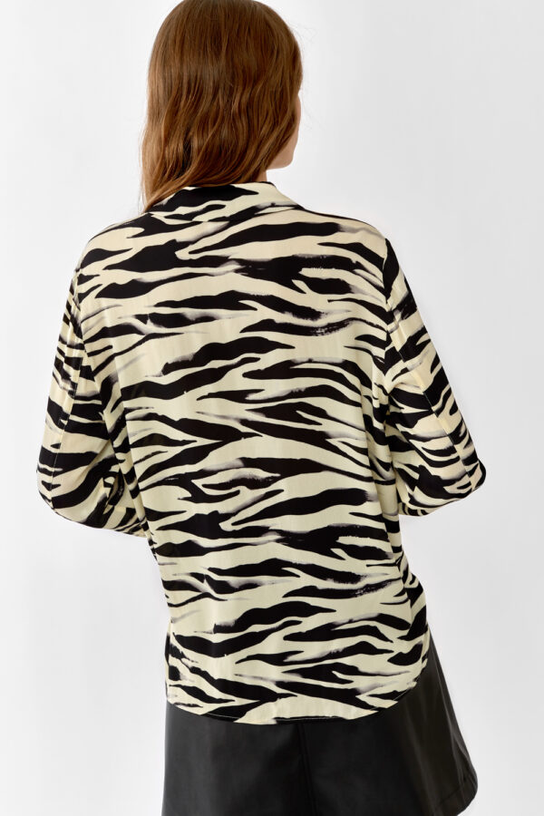 Woman wearing a yellow zebra printed shirt back