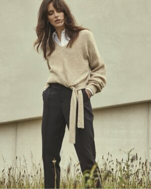 Woman wearing a beige V-neck knit with a white shirt and black trousers