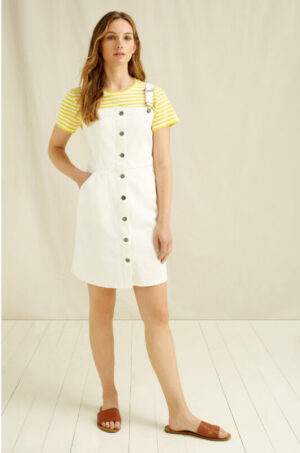Woman wearing a white dungaree dress with a yellow striped t-shirt