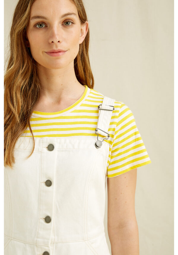 Detail of Woman wearing a white dungaree dress with a yellow striped t-shirt