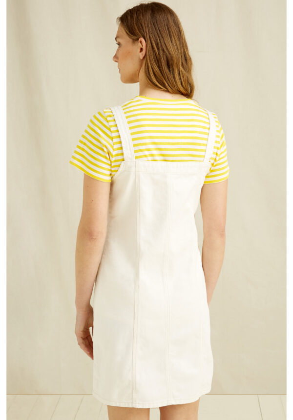 Back of Woman wearing a white dungaree dress with a yellow striped t-shirt