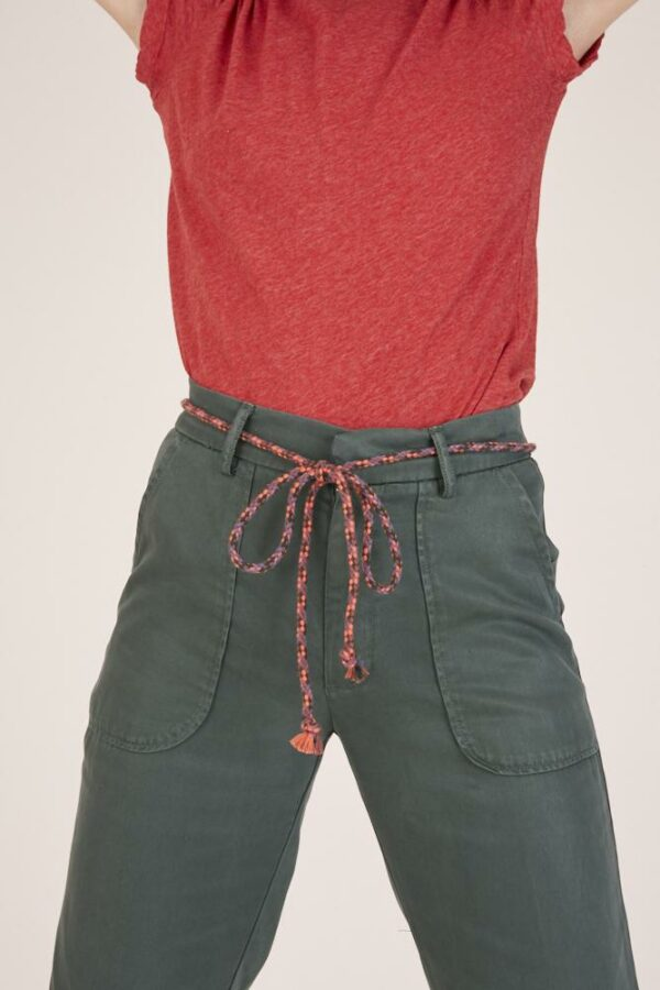 Woman wearing green trousers and a red t-shirt detail