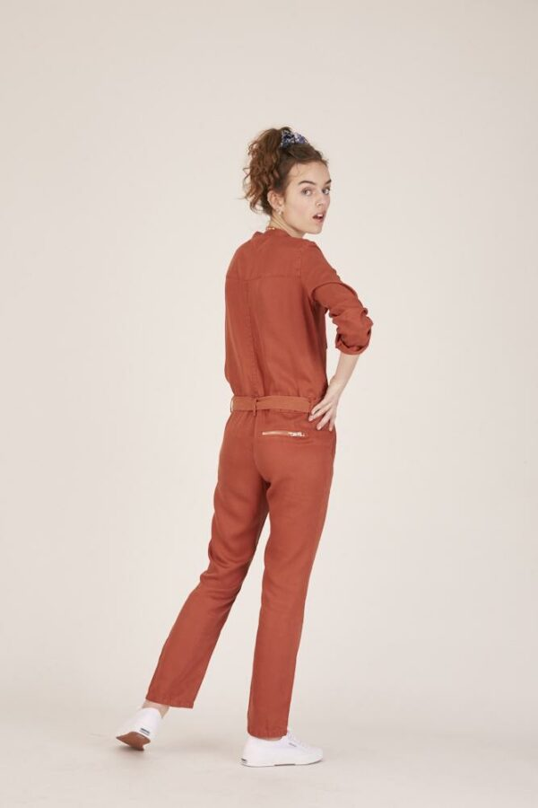 Woman wearing a red jumpsuit back