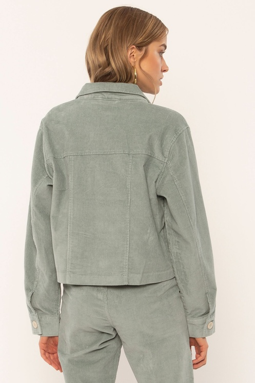 Woman wearing a blue grey corduroy jacket with matching pants back