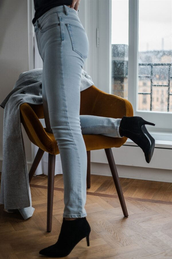 Woman standing in front of a window wearing a bleached blue skinny jeans and black boots