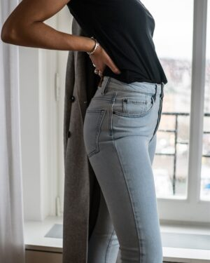 Woman standing in front of a window wearing a bleached blue skinny jeans and black top