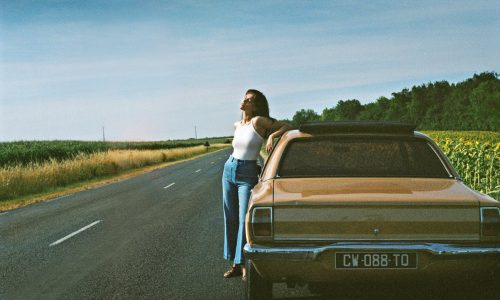 Woman standing next to a car wearing denim trousers and a white top