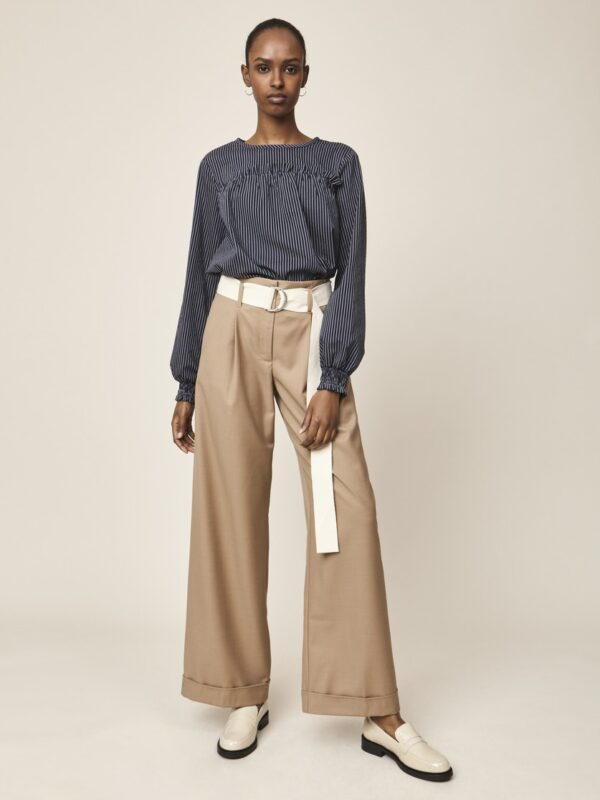 Woman wearing navy striped blouse and beige wide trousers