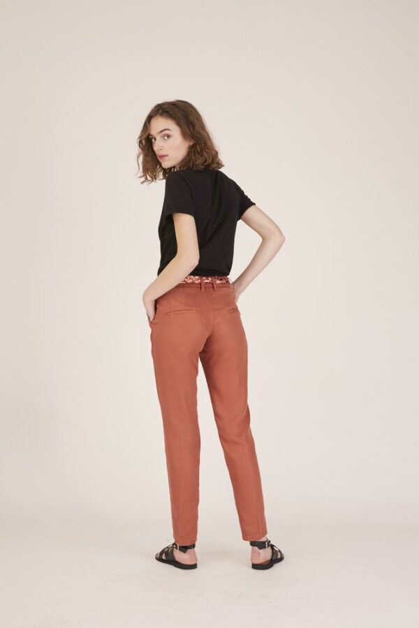 Woman wearing red trousers and a black t-shirt back