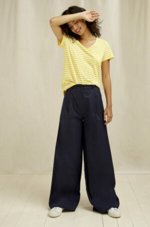 Women wearing a yellow striped V-neck t-shirt and wide trousers