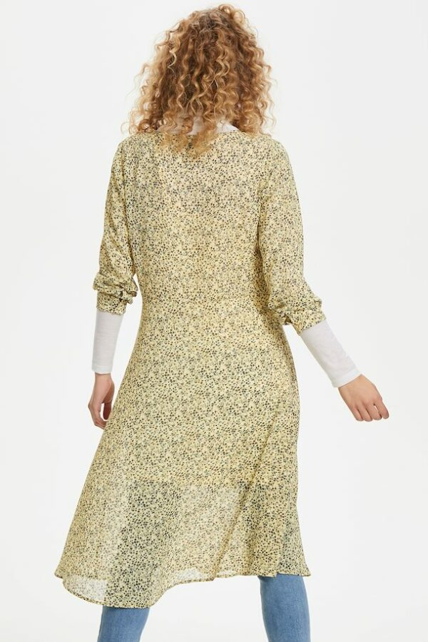 Blonde curly woman wearing a yellow flowered Agnes dress back