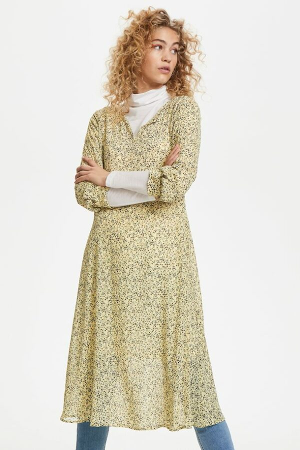 Blonde curly woman wearing a yellow flowered Agnes dress