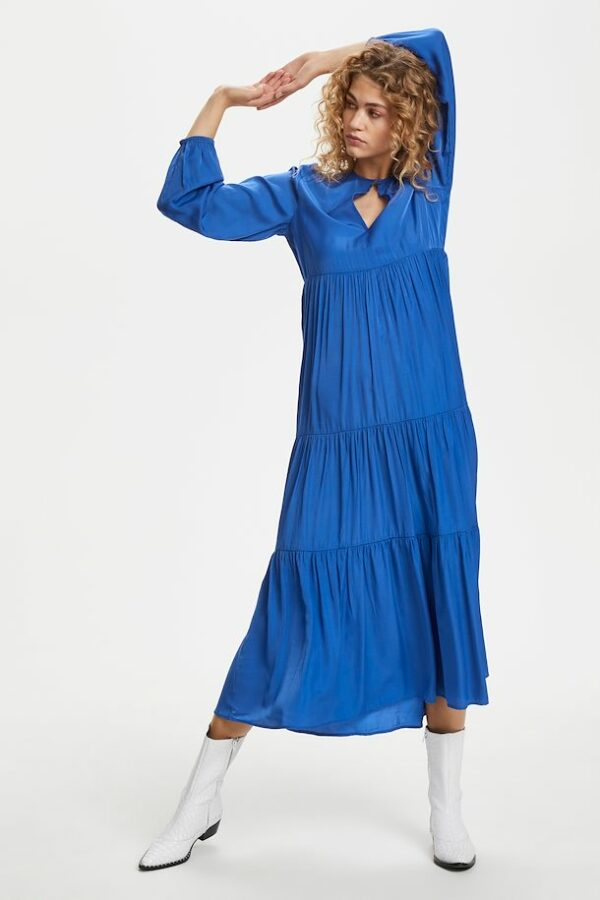 BBlonde woman wearing a long bright blue dress with white bootslonde