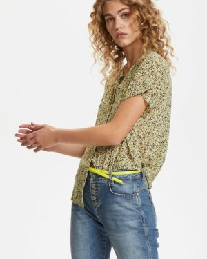 Blonde curly woman wearing a yellow flowered Felicia Agnes shirt on jeans back