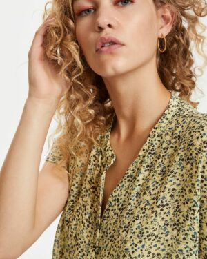 Blonde curly woman wearing a yellow flowered Felicia Agnes shirt