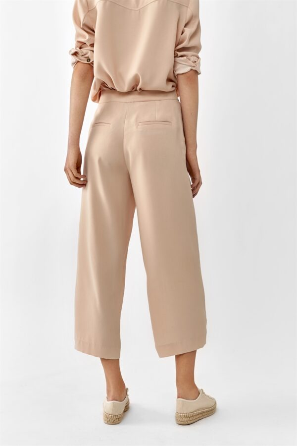 Women wearing a blush colored shirt and cropped wide trousers