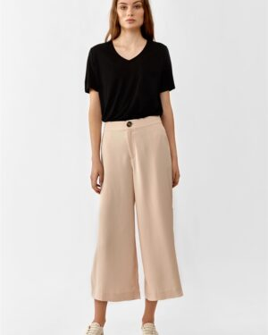 Women wearing a black V-neck t-shirt and cropped blush wide trousers