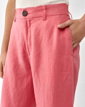 Detail of Women wearing pink linen trousers an a white top