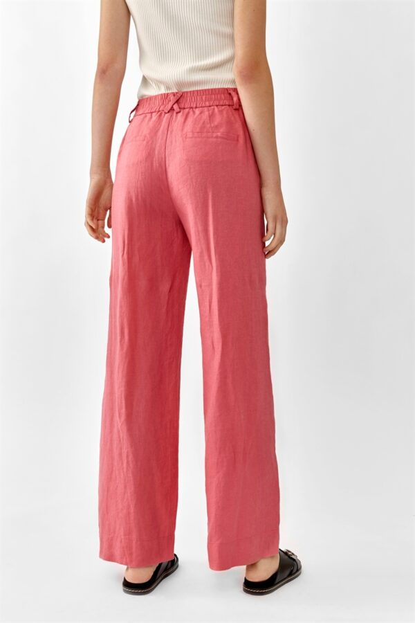 Back of Women wearing pink linen trousers an a white top