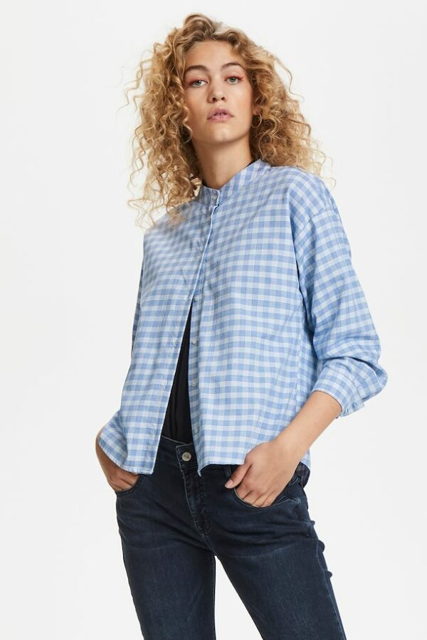 Blonde curly woman wearing a blue checked Milano shirt