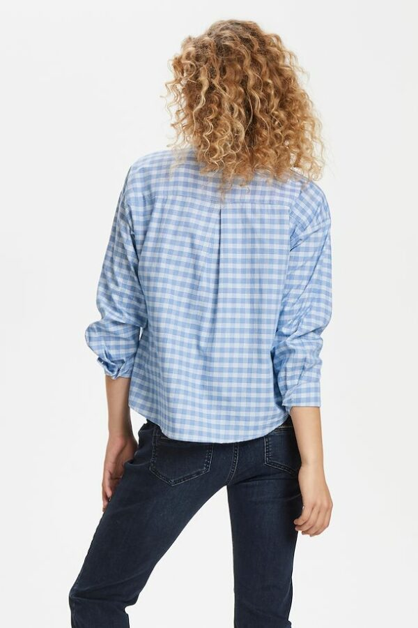 Blonde curly woman wearing a blue checked Milano shirt back