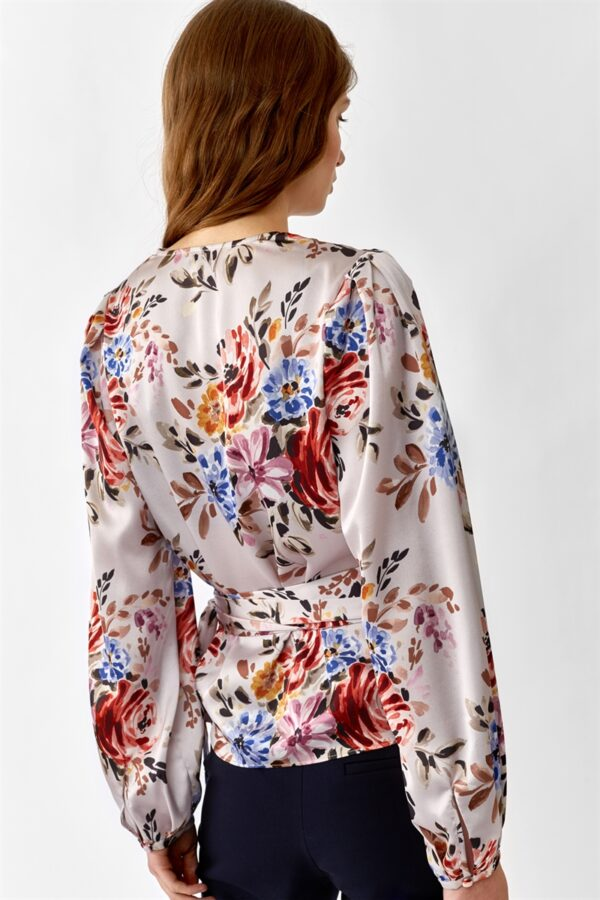 Back of woman wearing a pink flowered wrap blouse