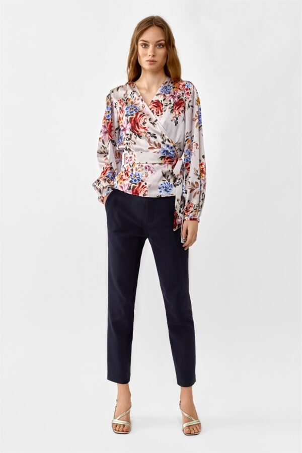 woman wearing a pink flowered wrap blouse and black trousers